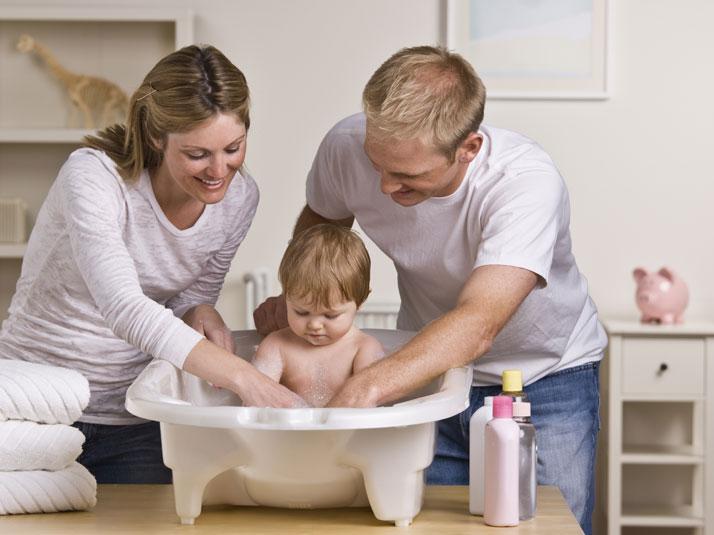 mamma e papà fanno il bagnetto al figlio