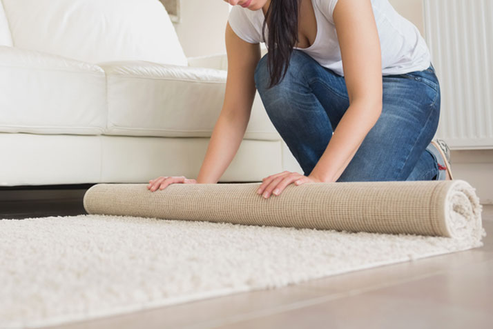 donna che toglie i tappeti